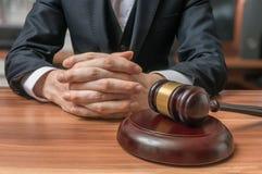 Advokaten har knäppt fast händer och auktionsklubban framme Rättvisa och lagbegrepp arkivfoto