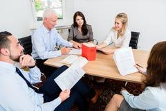 Advokater i advokatbyråläsningdokument och överenskommelser Royaltyfri Bild