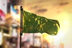 Adygea-Flagge gegen Stadt unscharfen Hintergrund an der Sonnenaufgang-Hintergrundbeleuchtung Stockfotos