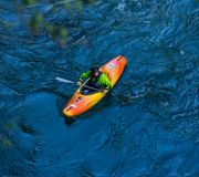 A kayaker goes down on a kayak on a mountain river Belaya in Adygea in the autumn time, the top view. Adygea, Russia - October 10, 2017: a kayaker goes down on a Royalty Free Stock Photography