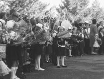 Happy children enrolled in the first class with gifts in their hands on the school`s solemn line in the day of knowledge, black a Stock Photos