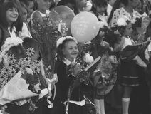Happy children enrolled in the first grade with gifts in hand with teachers and pupils at the school the solemn ruler in day of kn Stock Photo