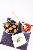 Adygeikäse mit Honig und Oliven Stockbilder