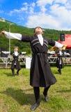 Adyghe-Junge in den Circassian nationalen Kostümen tanzen zum ethnischen Festival in den Bergen von Adygea Stockfotografie