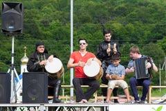 Adyghe-Musikensemble von den Circassian nationalen Kostümen, welche die Szene auf dem Hintergrund des grüner Waldethnischen Festi Stockbilder