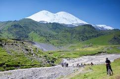 adyr高加索elbrus峡谷湖山区域su 俄国 2016年7月17日:Elbrus山夏天视图 山的游人 库存图片