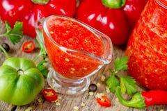 Adzhika de la pimienta roja en el barco de salsa de cristal Fotografía de archivo