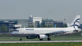 Aegean Airlines plane on runway in Munich Airport. Aegean Airlines jey getting ready to take off from Munich Airport. Air traffic control tower on background stock video