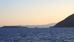 Aegean Mountains at Sunset, Greece. Silhouetted Aegean Greek Islands at sunset-dusk, with deep blue sea water and fading sky, Greece royalty free stock photo
