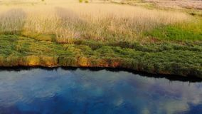 Aegean Rivers in the Spring. Drone ascending over the river looking towards the reed on the bank. Taken in  Akyaka Gulf of Gokova, Aegean Sea on a colorful stock footage