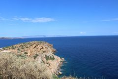 Aegean Sea Athens Greece. The Aegean Sea in Athens Greece. Blue ocean waters, blue skies and rugged cliffs stock photos