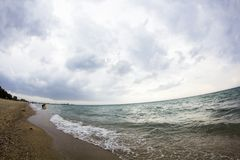 Aegean sea, beach and sky with clouds before the storm. Fish eye lens effect stock images