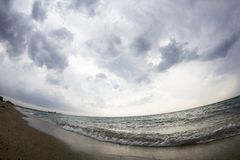 Aegean sea, beach and sky with clouds before the storm. Fish eye lens effect royalty free stock image