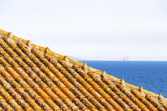 The Aegean Sea behind a roof at Kavala, Greece. Blurred Aegean Sea with an offshore platform behind a tiled building roof at Kavala, Eastern Macedonia, Northern royalty free stock photos