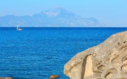 Aegean sea coast Chalkidiki, Greece. Aegean sea coast landscape and Mount Athos in mist, view from Orange Beach Chalkidiki, Greece. People on boat Stock Image