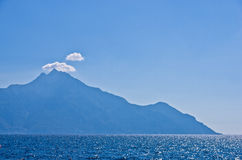 Aegean sea, silhouette of the holy mountains Athos and a small cloud above the mountain top Stock Images