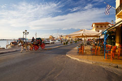 Aegina island. View of the seafront with coffee shops, bars and restaurants and a carriage pulled by a horse at Aegina seafront, Greece Royalty Free Stock Photos