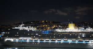 Aeial view. Big cruise ship with lighted lights stands in the port at night. Aeial view. Big cruise ship with lighted lights stands in the port at night stock footage