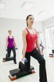 Aeróbicos femeninos del paso que hacen en gimnasio Foto de archivo libre de regalías