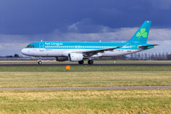 Aer Lingus Airbus A320. An Aer Lingus Airbus A320 taxiing at Schiphol Amsterdam Airport under dark clouds stock image