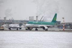 Aer Lingus doing taxi on snowy airport. Aer Lingus doing taxi on Munich Airport, MUC, snow on runway royalty free stock images