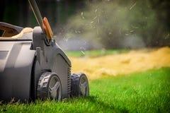 Aeração do gramado no jardim Gaseificador amarelo na grama verde imagens de stock royalty free