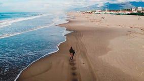 Aerail drone, Girl tourist runs along beach viareggio italy wave line in jeans. Freedom concept.  stock video footage