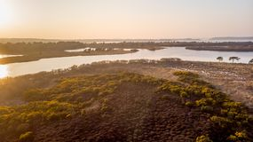 An aerail view of the Studland Nature Reserve with sand dune, peat bog and lake under a majestic hazy blue sky.  royalty free stock image