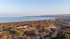An aerail view of the Studland Nature Reserve with sand dune, peat bog, sea and white cliff in the background under a majestic blu. E sky stock image