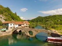 Aeralsikt till den gamla bron i byn Rijeka Crnojevica som reflekterar i vattnet i Montenegro mest stari royaltyfri bild