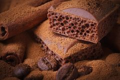 Aerated chocolate, coffee beans and cinnamon sticks closeup Royalty Free Stock Photos