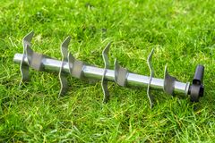 Aerating roller on the grass. Aerating steel roller on the green grass stock photo
