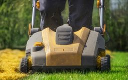 Aeration of the lawn in the garden. Yellow aerator on green grass. Close up royalty free stock image