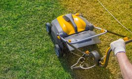 Aeration of the lawn in the garden. Yellow aerator on green grass. Close up stock photos