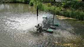 An aerator in service, adding oxygen into water in the pond. A green aerator in service. It floats on water and rotates turbine blades to add oxygen into water stock video footage
