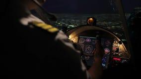 Aerei pilota attenti della direzione professionale, volo di notte sopra la megalopoli stock footage