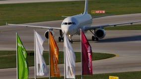 Aereo bianco che fa taxi sull'aeroporto di Monaco di Baviera, area delle bandiere stock footage