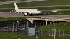 Aereo bianco che fa taxi sull'aeroporto di Monaco di Baviera, cielo blu video d archivio