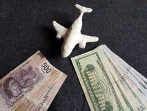 aereo bianco del plasticine, banconote messicane e banconote in dollari sulla tavola grigia Immagini Stock