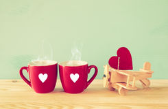 Aereo di legno con cuore accanto alle coppie delle tazze del coffe Fotografia Stock Libera da Diritti