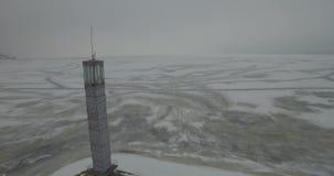 aereo Il faro in una calma e l'inverno desolato abbelliscono Una vista del segnale del faro da sopra Faro del fuco video d archivio