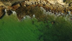 aereo Onde trasparenti sulla riva di pietra nel moto Algarve archivi video