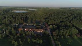 Aereo sorvolando un complesso del paese situato intorno ad una foresta ed ai laghi stock footage