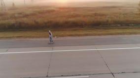 aereo un adolescente pattina su un pattino lungo una strada abbandonata fuori della città all'alba Ragazza in una maglietta felpa stock footage
