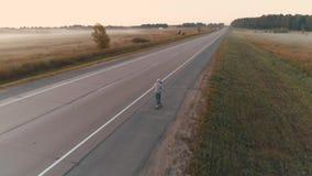 aereo un adolescente pattina su un pattino lungo una strada abbandonata fuori della città all'alba Ragazza in una maglietta felpa archivi video