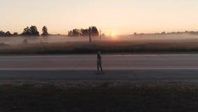 aereo una ragazza sta guidando su un pattino lungo una strada principale abbandonata all'alba stock footage