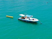 Aeria view of sport fishing boat with banana boat ride attach on the back. Sport fishing boat with banana boat ride attach on the back. In Praia do Forte beach stock photography