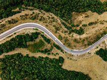 Aerial Above View Of A Rural Landscape With A Curvy Road Running Through It In Greece.