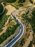 Aerial above view of a rural landscape with a curvy road running through it in Greece. Drone photography Stock Photography