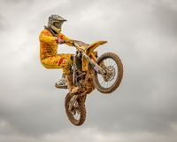 Aerial acrobat during a motocross race. Motorcross first evolved in the U.K. from motorcycle trials competitions, such as the Auto-Cycle Clubs`s first quarterly stock photography